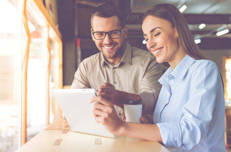 Handsome businessman and beautiful business lady are using a digital tablet, drinking coffee and smiling while co-working Stock Photo