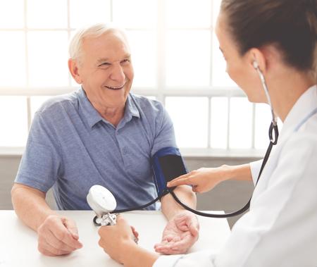 De knappe oude mens heeft zijn geteste bloeddruk en glimlacht terwijl het zitten bij de arts