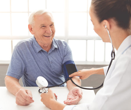 Hübscher alter Mann lässt seinen Blutdruck prüfen und beim Sitzen am Arzt lächeln Standard-Bild - 65186882