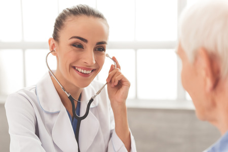 sound therapist: Beautiful female doctor in white medical coat is consulting her old patient, using a stethoscope and smiling while sitting in office
