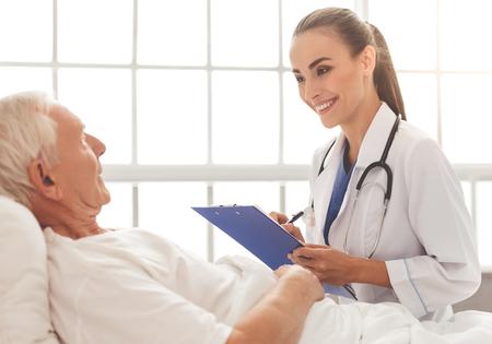 Hermosa doctora en bata blanca médica está escuchando a su viejo paciente, haciendo notas y sonriendo Foto de archivo