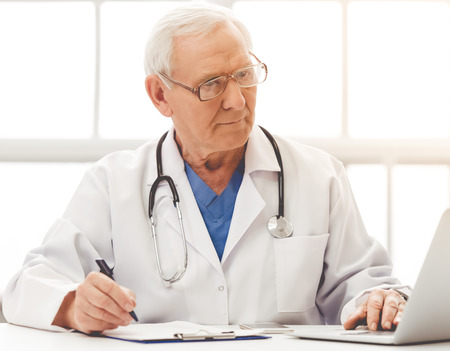 Handsome old doctor in white medical coat and eyeglasses is using a laptop, making notes and smiling while sitting in his office