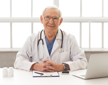 Handsome old doctor in white medical coat and eyeglasses is looking at camera and smiling while sitting in his office Stock Photo