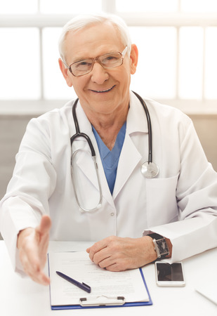 Handsome old doctor in white medical coat and eyeglasses is offering his hand, looking at camera and smiling while sitting in his office