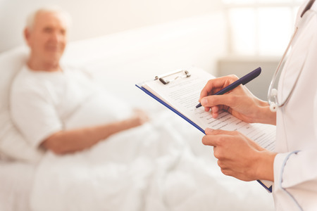 Cropped image of beautiful female doctor in white medical coat listening to her old patient and making notes