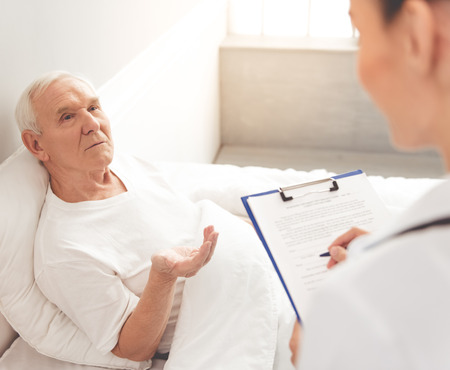 hospital notes: Handsome old patient is talking to his doctor while lying in bed in hospital. Doctor is making notes