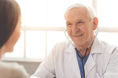 sound therapist: Handsome old doctor in white medical coat is using a stethoscope, consulting his patient and smiling while sitting in his office Stock Photo