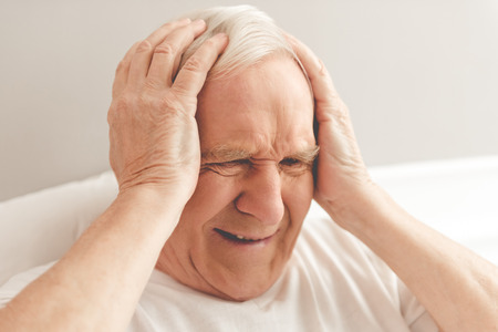 he old: Handsome old man is having a headache. He is holding his hands on head, lying in bed in hospital