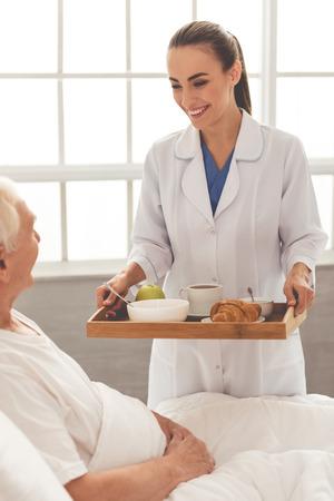 Belle infirmière en blouse médicale blanche tient un plateau avec le petit-déjeuner pour l'ancien patient. Les deux sourient