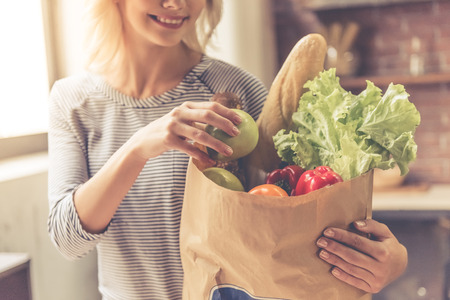 Cropped image of beautiful girl holding a paper shopping bag with food and smiling while standing in kitchen at home Stock Photo