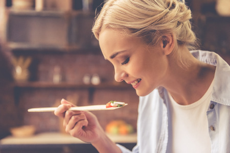 Mooi meisje is aan het proeven van eten en glimlachen tijdens het koken in de keuken thuis