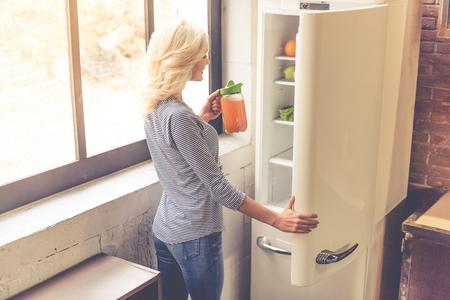 Kühlschrank Krug : Schönes mädchen hält einen krug saft betrachtet kamera und lächelt