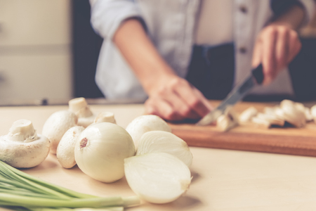 Food on kitchen table, in the background girl is cutting mushrooms while cooking Stock Photo