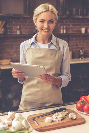 Beautiful girl in apron is using a tablet, looking at camera and smiling while cooking in kitchen at home