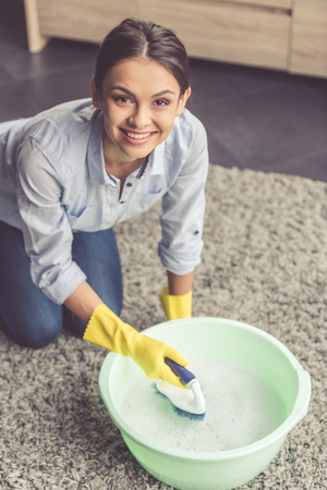 soapsuds: Beautiful young woman is using a brush and basin with soapsuds, looking at camera and smiling while cleaning carpet in the house