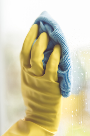 Woman is using a duster while cleaning windows in the house, close-up