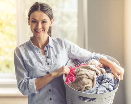 아름 다운 젊은 여자는 세탁기와 분지를 잡고 카메라를보고 집에 서있는 동안 웃 고