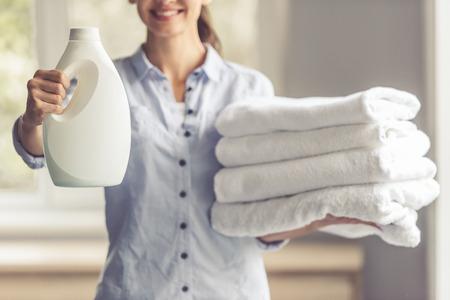 아름 다운 젊은 여자 웃 고, 직물 연화제 및 깨끗 한 수건의 잘린 된 이미지