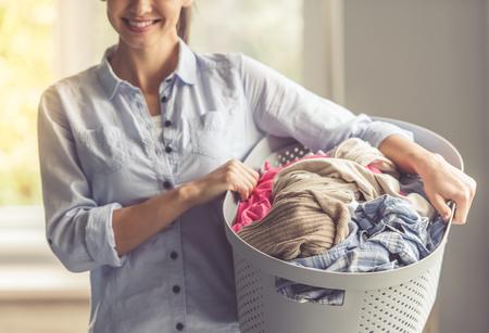 ランドリー、洗面器を押しながらホームで立ちながら笑顔の美しい若い女性のトリミングされた画像 写真素材