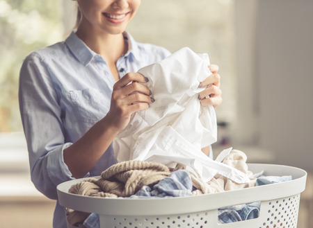 chores: Cropped image of beautiful young woman is smiling while doing laundry at home Stock Photo