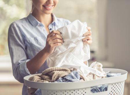 Imagen recortada de una mujer hermosa joven está sonriendo mientras que lavar la ropa en el hogar Foto de archivo - 65422817
