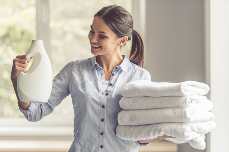 Beautiful young woman is holding a fabric softener and clean towels, looking at the bottle and smiling Reklamní fotografie