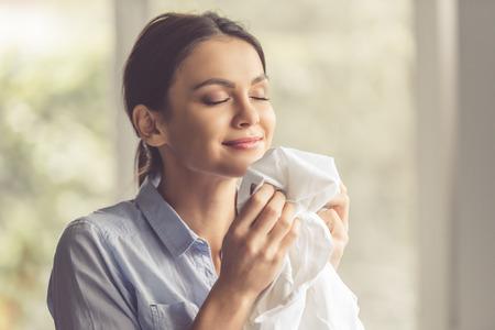 lavando ropa: Joven y bella mujer está oliendo ropa limpia y sonriendo mientras lavar la ropa en el hogar