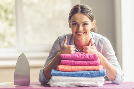 Beautiful young woman is leaning on ironing board, showing Ok sign, looking at camera and smiling while ironing clothes at home