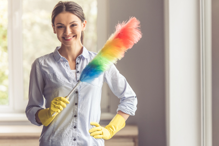 Beautiful young woman in protective gloves is holding a static duster, looking at camera and smiling while cleaning her house Stock Photo
