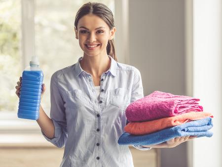 Schöne junge Frau hält ein Weichspüler und saubere Handtücher, die Kamera und das Lächeln