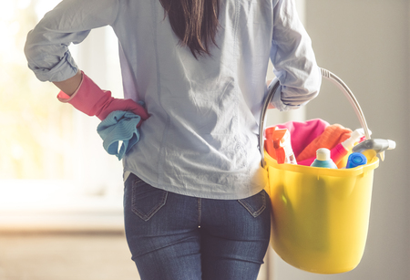 Back view of beautiful woman in protective gloves holding a bucket with detergents and rags while cleaning her house