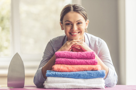 Mooie jonge vrouw leunt op strijkplank, kijkt naar de camera en lacht terwijl thuis kleding strijkt