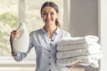 Beautiful young woman is holding a fabric softener and clean towels, looking at camera and smiling