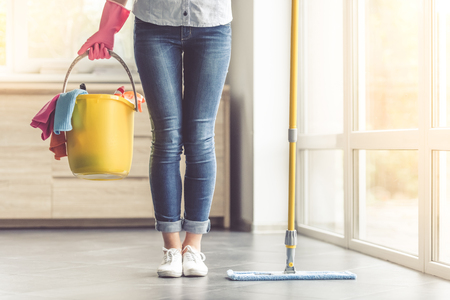 cropped image: Cropped image of beautiful woman in protective gloves holding a flat wet-mop and bucket with detergents and rags while cleaning her house Stock Photo
