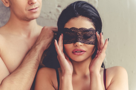 nackter junge: Beautiful passionate couple is having sex on bed. Man is holding a lace bandage on his beautiful partners eyes