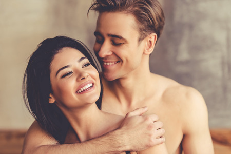 Beautiful young couple is hugging and smiling while having on bed