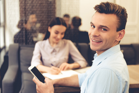 Handsome young businessman is using a smartphone, looking at camera and smiling while working with his partner in office Stock Photo