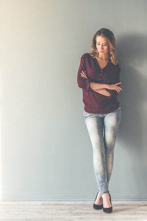 Full length portrait of beautiful stylish young woman posing and smiling, on gray background