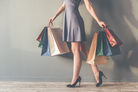 high heeled shoes: Cropped image of beautiful stylish young woman in cocktail dress and high heeled shoes holding shopping bags, on gray background