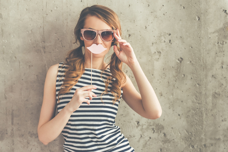 striped vest: Stylish young woman in sun glasses is holding a paper lips on stick and looking at camera, on beton wall background