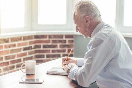 Hübscher reifer Geschäftsmann im Gesellschaftsanzug schreibt in sein Notizbuch beim Arbeiten im Büro