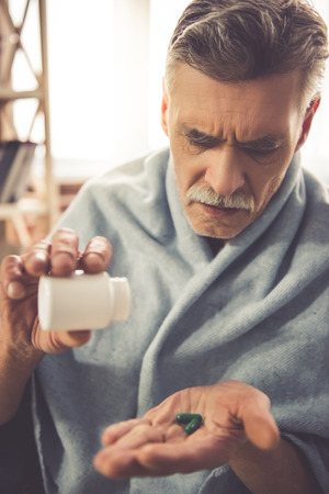senior men: Handsome ill mature man is taking pills while sitting wrapped in blanket at home