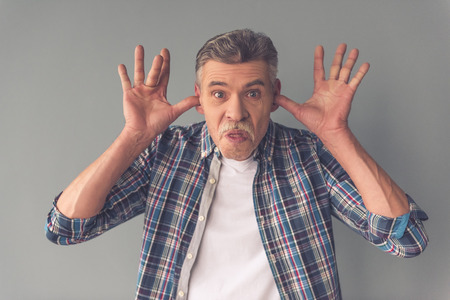 theatrics: Handsome funny mature man in casual wear is making faces on camera, on gray background