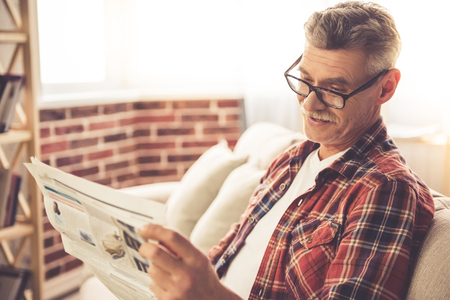 Handsome mature man in casual clothes is reading a newspaper and smiling while resting at home