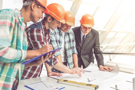 drafts: Handsome construction workers in protective helmets are studying drafts in the office center Stock Photo