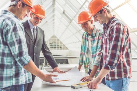 Gut aussehend Bauarbeiter in Schutzhelmen studieren Zugluft im Büro-Center photo
