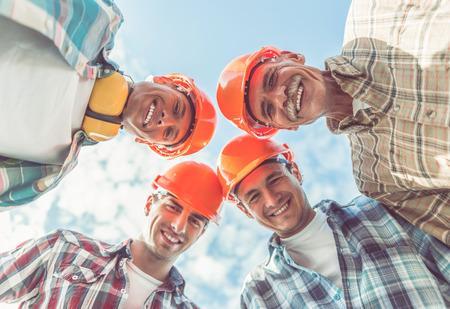 Ansicht von unten gut aussehend Bauteam in Schutzhelmen in die Kamera und lächelnd, während draußen stehen photo