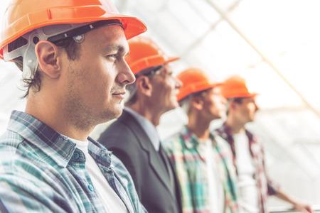 Seitenansicht der schönen Bau-Team in Schutzhelmen im Büro Zentrum stehen photo