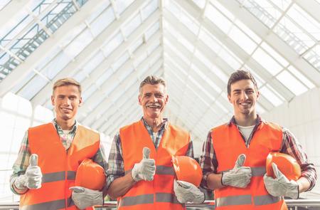 Portrait der schönen Bau-Team in Schutzhelmen und Westen im Büro Zentrum stehen photo