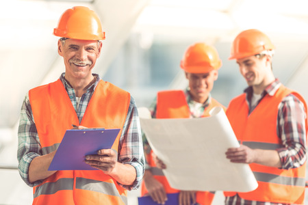 Gut aussehend Bauarbeiter in Schutzhelmen und Westen studieren Zugluft im Büro-Center photo